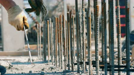 cement floor : One man works with metal construction on a site. Stock Footage