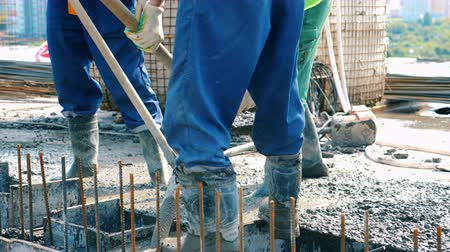 hormigonera : Workers levelling concrete on a floor.