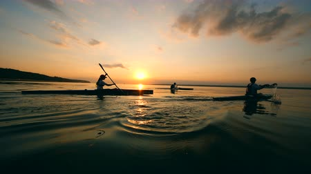 каноэ : Sportsmen are canoeing across the sunset lake