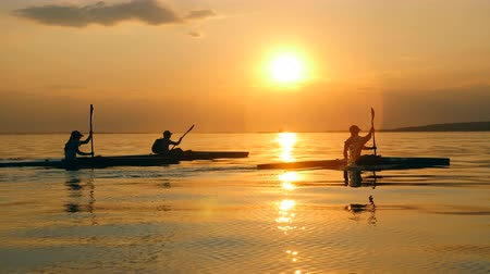 kano : Sunset waterscape with paddlers sailing along it