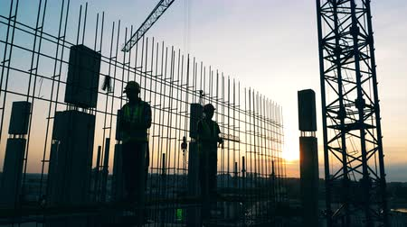armature : Men work on a construction site on a sky background. Stock Footage