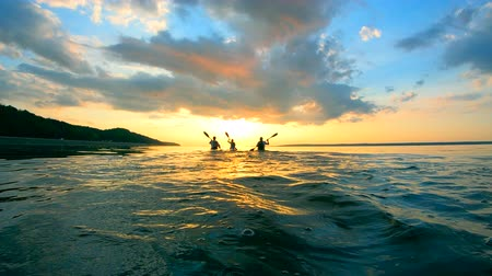 каноэ : Group of paddlers are kayaking into the sunset