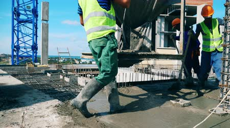 bewehrung : Workers pour concrete onto a floor, leveling it.
