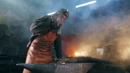 enterprise : Hammersmith is beating iron with a hammer in slow motion