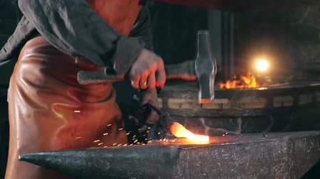olvasztott : Smithy worker is beating heated metal with a hammer Stock mozgókép