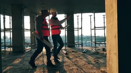 прораб : Two men walk in a building on a site. Стоковые видеозаписи