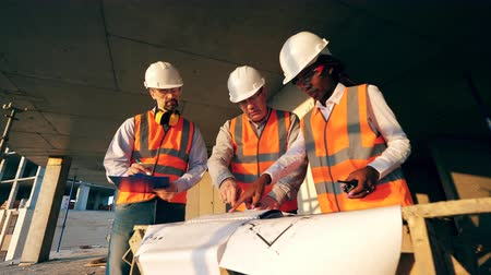felügyelő : Three workers look at a blueprint on a construction site. Construction workers at modern construction site.