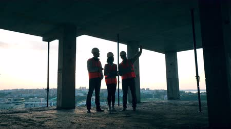 vest : A team of engineers talking on a construction site.