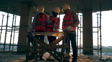 прораб : Construction workers at modern construction site. Smiling engineers look at a blueprint on a building site.