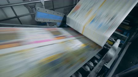 stationary : Printing press with uncut magazine pages going through it