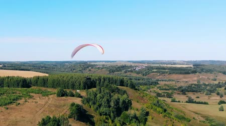 parachuting : Paraglider is lowering and flying over the forest