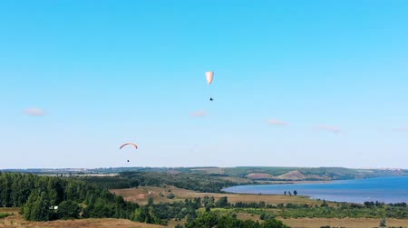 parachuting : People are flying with ram-air parachutes above the ground