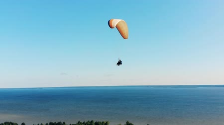 padák : Two people are flying above the water on the paraplane
