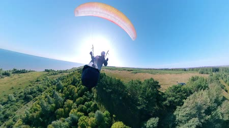 parachuting : Front view of a person flying with a ram-air parachute. Man Paragliding, beautiful nature background.