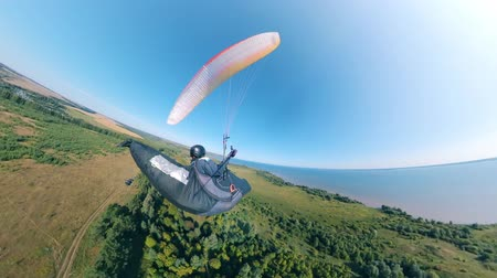 equipped : Green land and a person flying over it on the paraplane Stock Footage