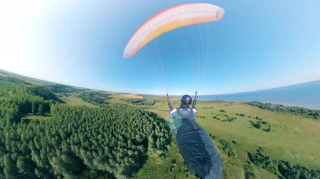 equipped : Backside view of a person having a paragliding flight