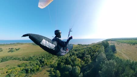 equipped : Paragliding flight over the land held by a person