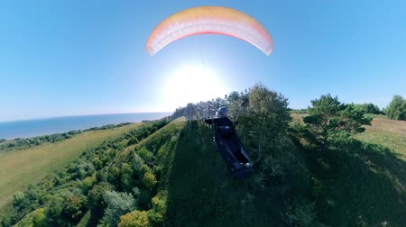 equipped : A person is paragliding closely to the ground