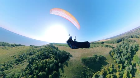 magasság : A person is flying with a ram-air parachute above the fields. Man Paragliding, beautiful nature background.