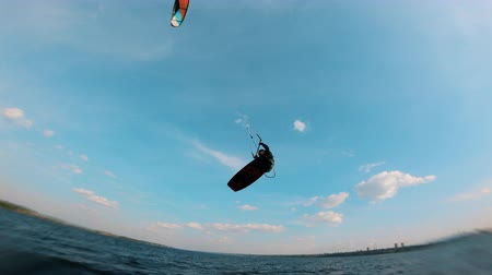 pulando : Person jumps while riding a kiteboard.