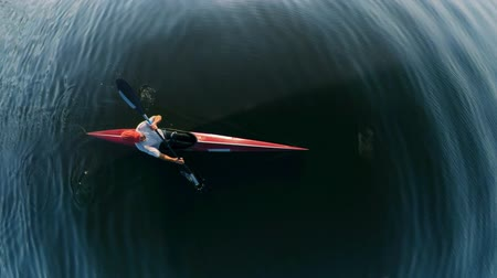 evezős : Top view of water surface and a man kayaking through it