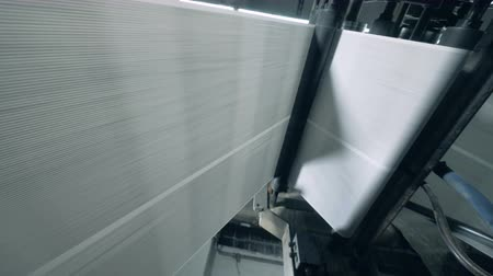 不在 : White sheets rolled on a conveyor in printing office.