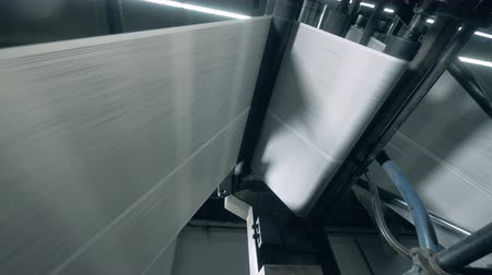 kartka papieru : Paper going on a rolling conveyor at printing office.