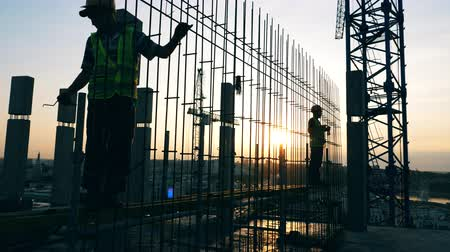 кирпичная кладка : Sunset construction site with engineers fabricating a framework Стоковые видеозаписи