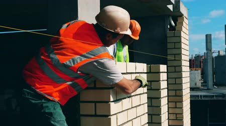 кирпичная кладка : Brick wall is getting processed by construction workers Стоковые видеозаписи