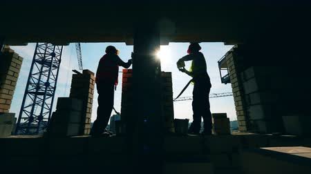 kamenné zdivo : Construction of the brick wall made by backlit builders