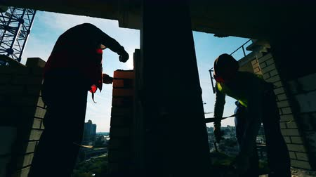 trabajos manuales : Masonry works held by two engineers in a high-rise building