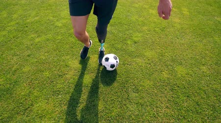 paralympics : Green lawn with a physically challenged man playing soccer, football