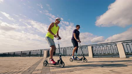 hátrány : Men with leg substitutes are riding scooters outdoors