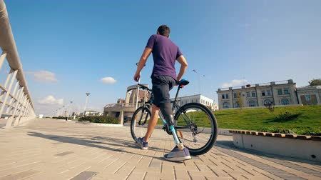 desvantagem : A man with a leg substitute is walking with a bike