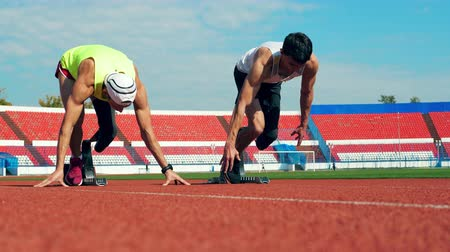desvantagem : Two runners with artificial legs are practicing