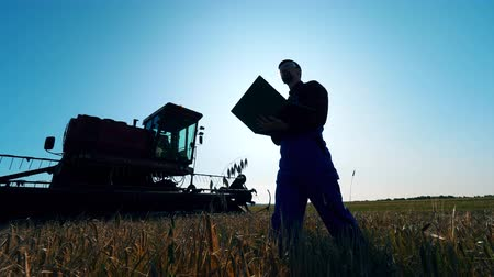 agronomist : Agriscientist with a laptop is near the combine machine
