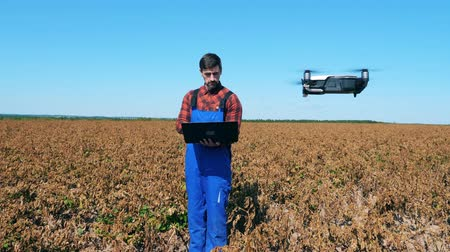 herbicides : Agriculturist is navigating a drone in the faded field