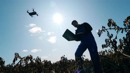 herbicides : Male agronomist is operating a drone from the laptop