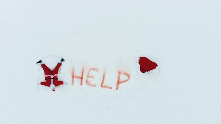 sós : Santa Claus is making a snow angel next to a help sign