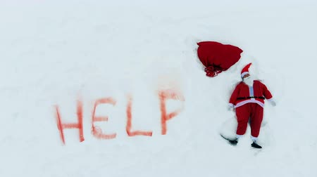 sos : Snows, help sign and Santa Claus making a snow angel