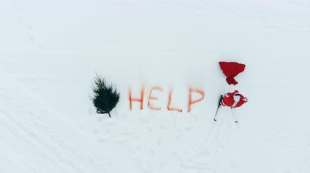 sós : Top view of Santa Claus yelling next to a help sign