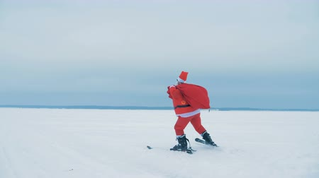 povinnost : Santa Claus is skiing with a bag of presents across the snow Dostupné videozáznamy