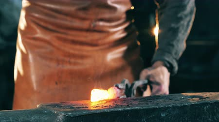 demirci : Professional blacksmith shaping knife on anvil.