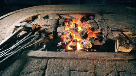 chama : Metal tools lying near fire at forge. Stock Footage