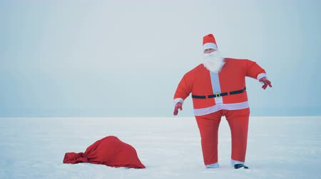 polo nord : Santa Claus is jumping in the snow next to his bag with presents Filmati Stock