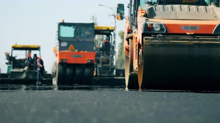 roadworks : Road rollers work on a road during paving.