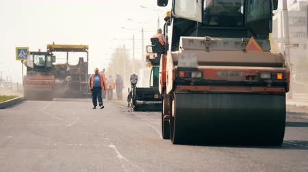 sous sol : Workers and rolling machines lay asphaly on a road. Vidéos Libres De Droits