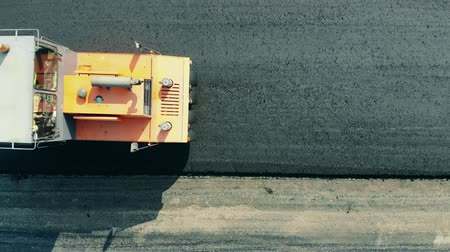 roadworks : One machine rolls asphalt on a road.