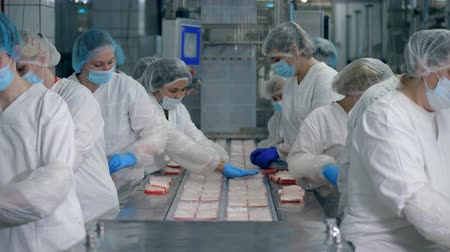ração : Packaging process of fish snacks carried out by female food factory workers