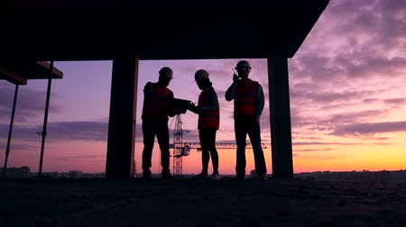 unfinished : Team of engineers are working at the sunset building lot Stock Footage